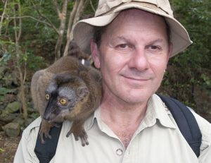 Photo of author Alan Dean Foster with a lemur on his shoulder.
